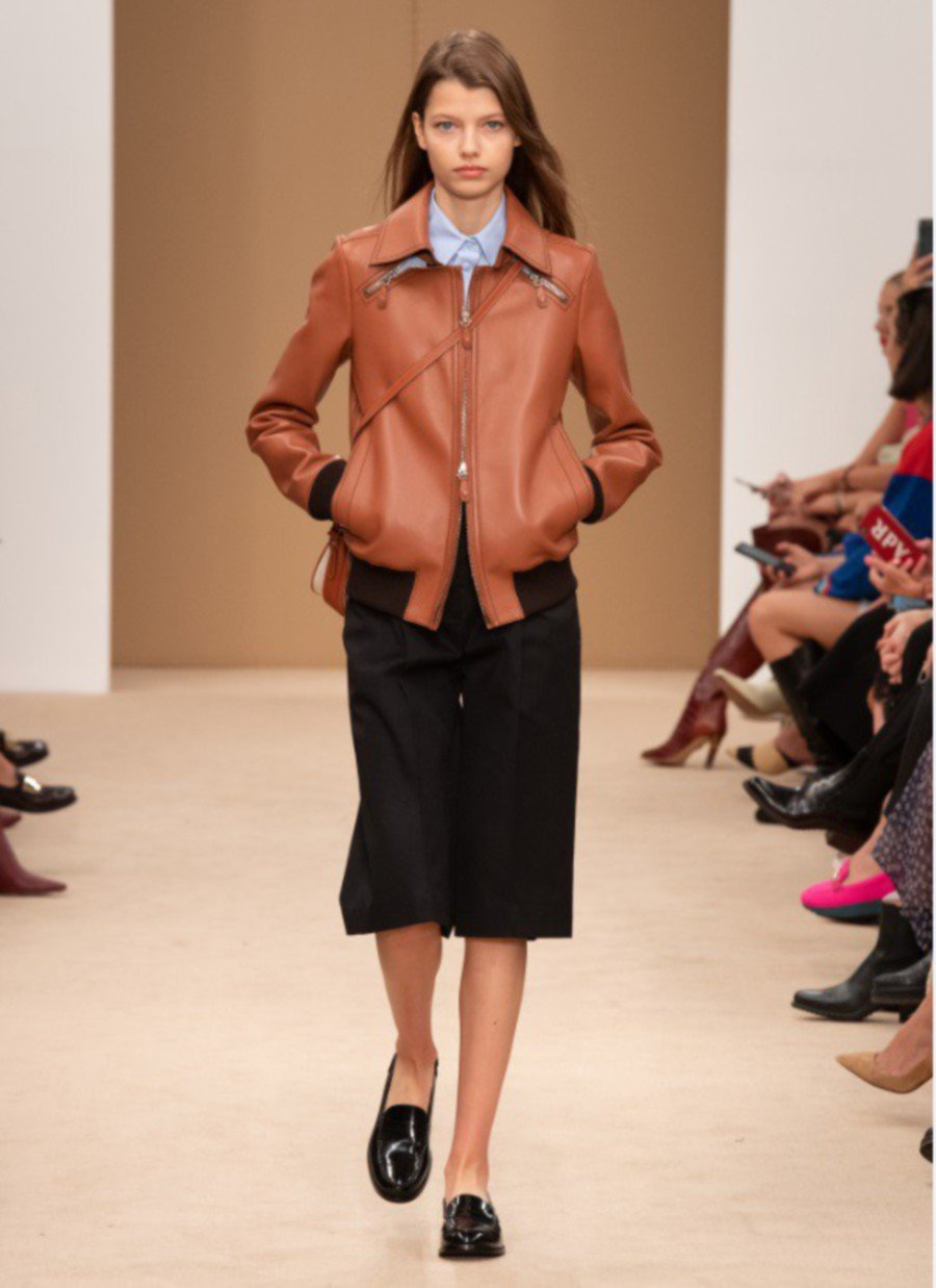 The brand employs beautiful craftsmanship in this brown blouson jacket, worn with black culottes.
