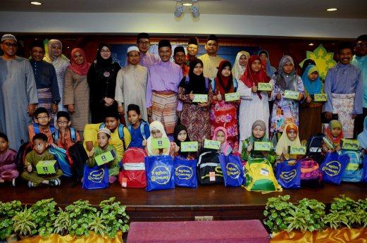 Selangor and Federal Territory Anak-anak Terengganu Association (Pesat) president Datuk Wan Husin Wan Embong presenting goodies to orphans from SK Tok Jiring at the buka puasa at Primula Beach Hotel. Pix by MOHD SYAFIQ AMBAK