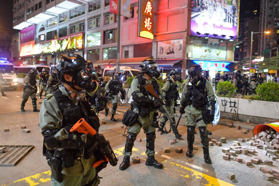 Riot police stand on a street as protesters and pedestrians gathered near the Mong Kok police station in Hong Kong. - AFP