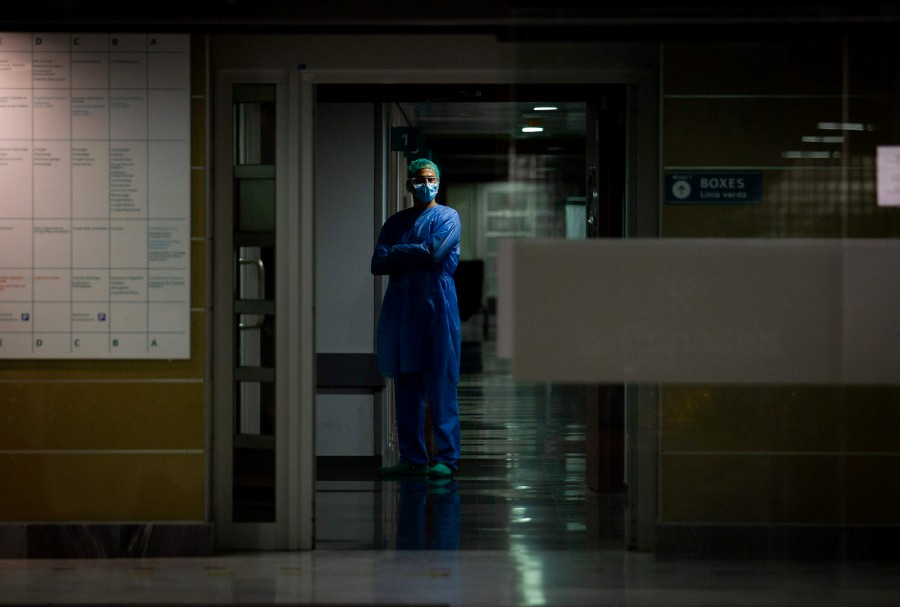 A healthcare worker dealing with the new coronavirus crisis stands in a corridor of Son Espases Hospital in Palma de Mallorca. -AFP pic