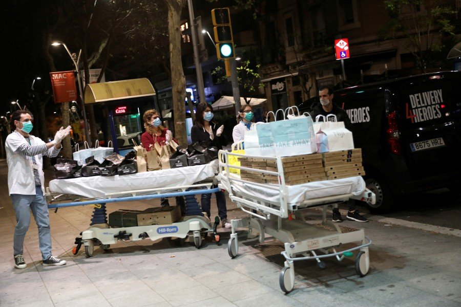 Health workers collect food from Delivery 4 Heroes on stretchers at Clinic hospital, during the outbreak of coronavirus disease (COVID-19) as near two hundred dinners are being delivered per day to Medical Staff as a gesture of thanks from the City's Takeaway Businesses, in Barcelona, Spain. -REUTERS pic