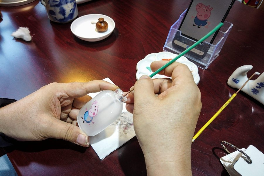 """This picture shows Chinese artist Wei Dongfang drawing a Peppa Pig figure inside a snuff bottle at his workshop on Nanluoguxiang Street in the centre of Beijing. - To keep alive the centuries-old art known as """"guihuahu"""", or """"bottle painted by ghosts"""", some painters are appealing to younger tastes with modern motifs -- including the popular children's character Peppa Pig. (Photo by Leo RAMIREZ / AFP)"""