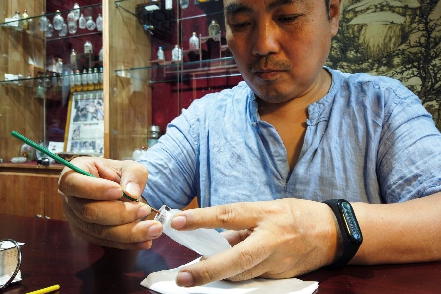 This picture shows Chinese artist Wei Dongfang drawing on a snuff bottle at his workshop on Nanluoguxiang Street in the centre of Beijing. (Photo by Leo RAMIREZ / AFP)
