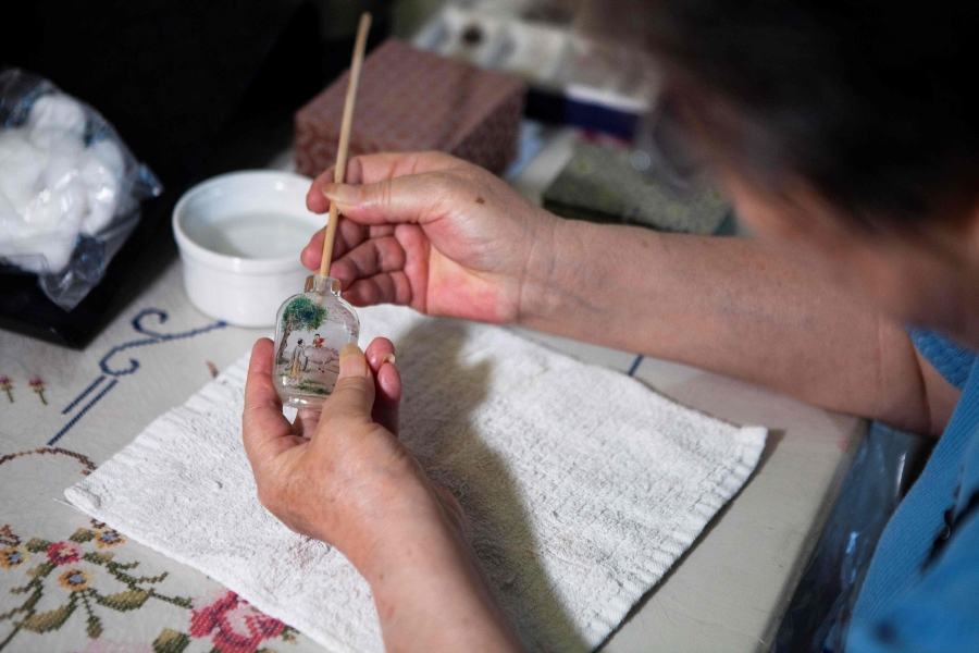 This picture taken on July 1, 2019 shows artist Zhang Yuhua painting a snuff bottle at her home in Beijing. Delicate designs painted on the inside of miniature Chinese snuff bottles by artists like Zhang Yuhua and her husband Gu Qun usually feature calligraphy, floral compositions and traditional rural scenes. (Photo by Leo RAMIREZ / AFP)