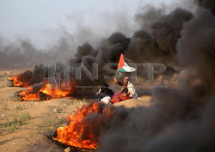a palestinian woman waves a national flag near burning tyres during clashes along the israeli border fence east of gaza city on september 28 2018