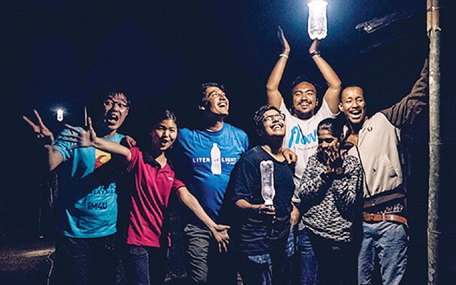 Volunteers bringing light to a village under the Liter of Light project