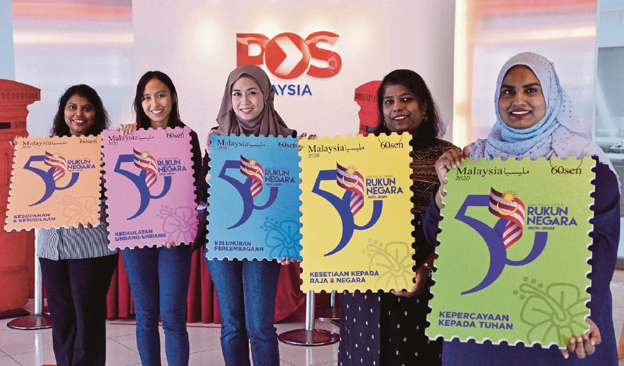 Pos Malaysia personnel with replicas of the special edition stamps launched in  conjunction with the 50th anniversary of Rukun Negara in Kuala Lumpur. -BERNAMA pic
