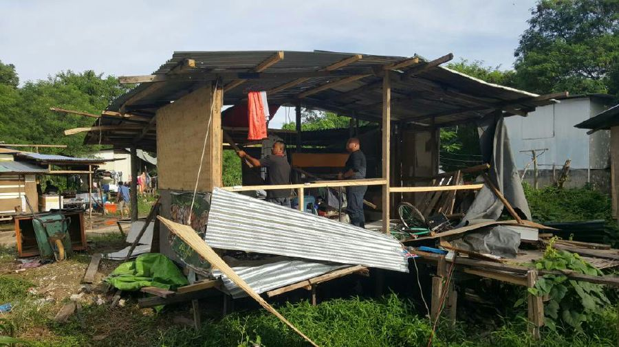 Kota Kinabalu City Hall enforcement personnel tearing down two squatter homes. Pix courtesy of police.