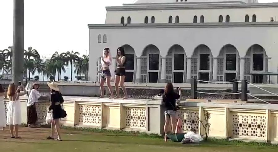A screen grab of a10-second video showing two women, believed to be foreigners, inappropriately dressed and showcasing some sexy K-pop dance moves on the wall of the mosque. Pix courtesy of NST Reader