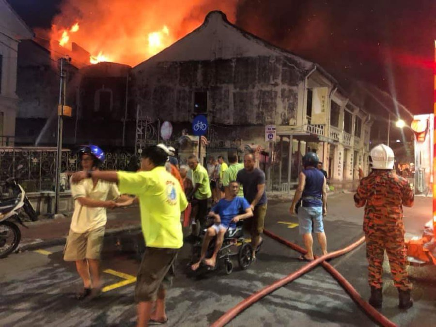 Firemen and volunteers help evacuate residents of the old folks' home in Lebuh Carnavon. - NSTP/Courtesy of Fire and Rescue Dept.