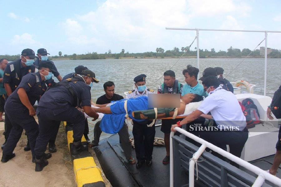 Malaysian Maritime Enforcement Agency (MMEA) personnel help carry Muhammad Aiman Alias, who will be transfered to the Besut Hospital. - Pic courtesy of MMEA