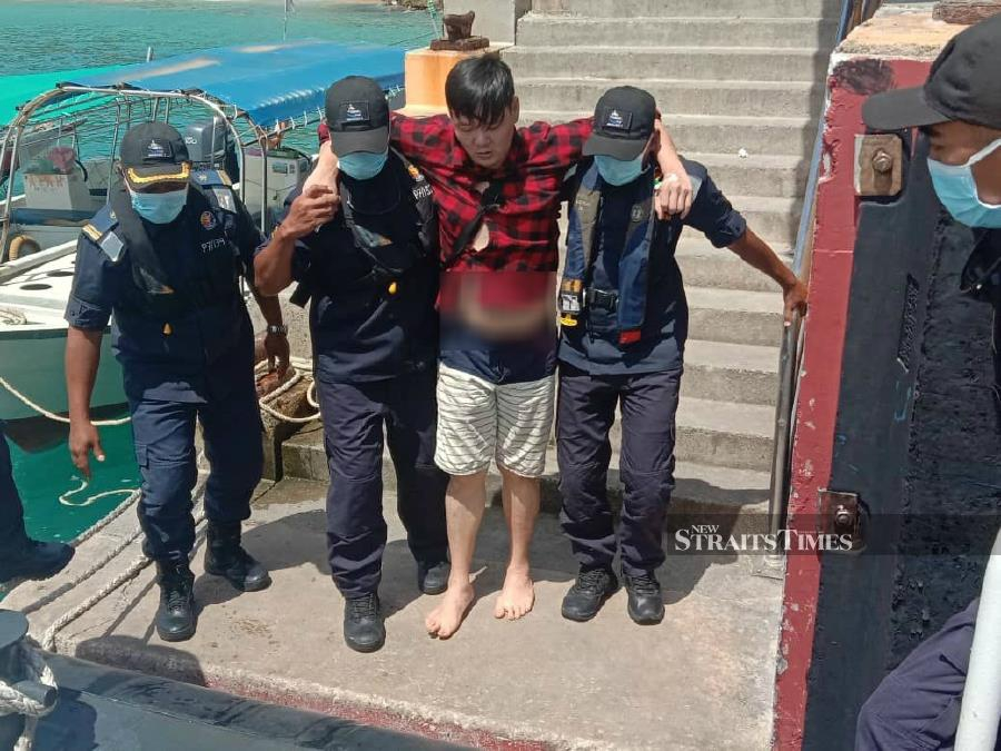 Malaysian Maritime Enforcement Agency (MMEA) personnel help Chaan Chee Keong. - Pic courtesy of MMEA