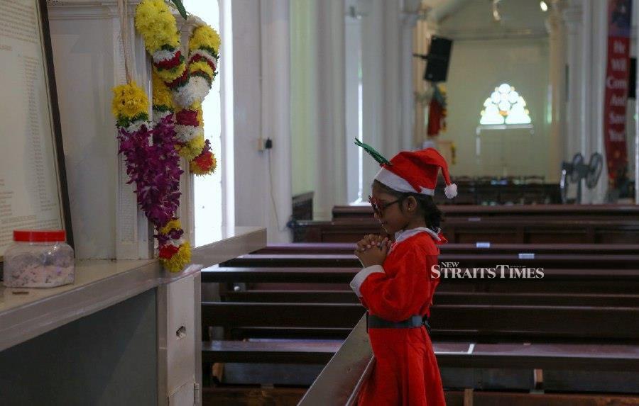 Tashvinii Khalidass offers her prayers at St Anthony Church in Jalan Pudu in Kuala Lumpur. - NSTP/HAZREEN MOHAMAD