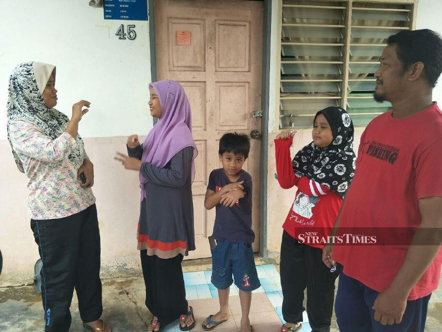The couple's third child Nor Ain Mohd Arihan, 12 (2nd from left), said there was not much difference compared to verbal communication when it comes to the use of sign language when they 'talk' with their parents.  - STR/RAMLI IBRAHIM