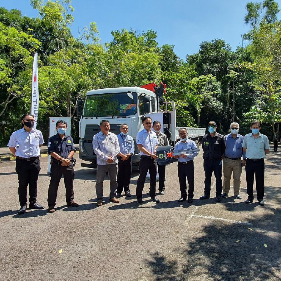 Sabah Wildlife Department director Augustine Tuuga (fourth right) receives key replica of Nissan 10-tonne truck from representatives of Tan Chong Motor
