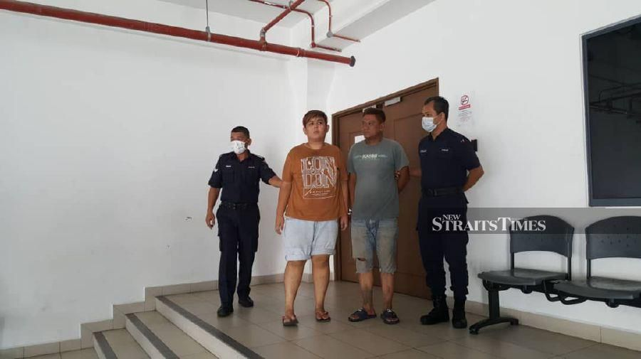 The duo are escorted by policemen after the trial at Kota Kinabalu Magistrate's Court. - NSTP/JUWAN RIDUAN