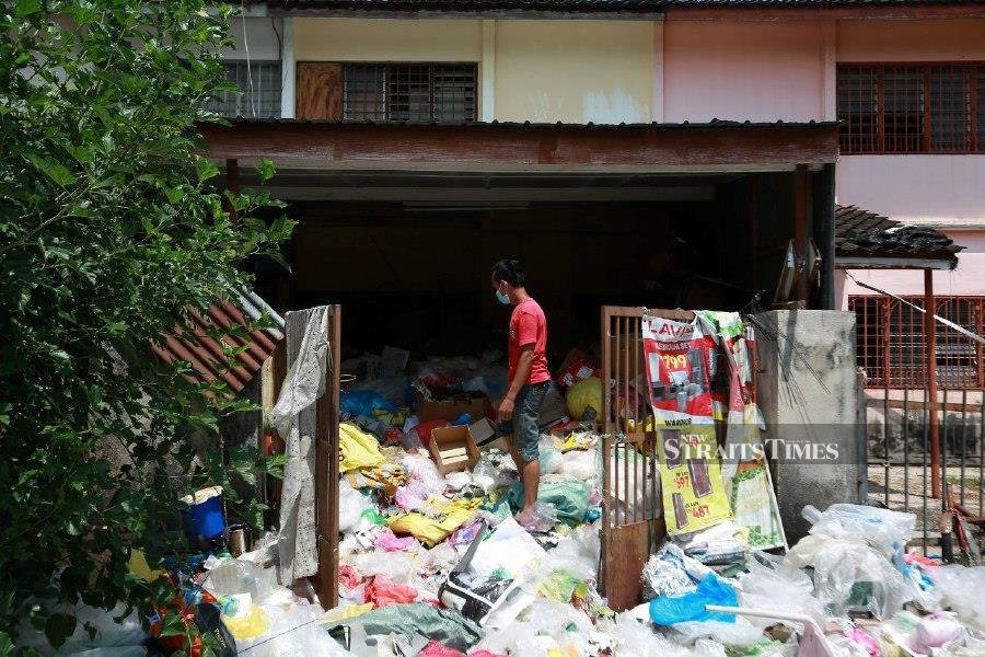 Sulaiman Abd Majid, tries to clean the pile of rubbish at Taman Bersatu, Simpang Pulai. -NSTP/SHARUL HAFIZ ZAM