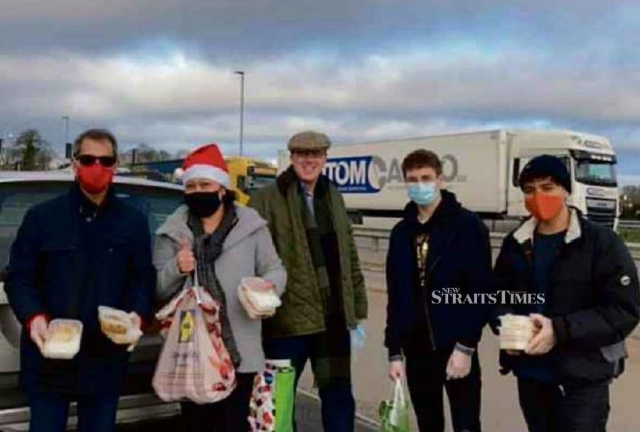 Lizana Moha with her husband Charles Woodgate and her team of volunteers by a motorway in Kent, England. - NSTP/ZAHARAH OTHMAN
