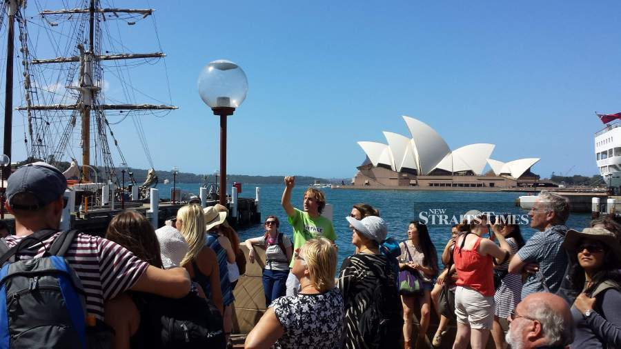 Pickrell (in bright green t-shirt) explaining the history of Circular Quay to a group of I'm Free Walking Tour participants.