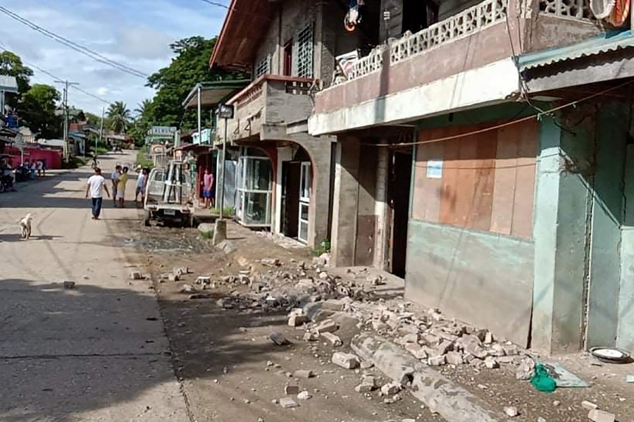 This handout photo received on August 18, 2020 from the Facebook page of Jake Gabilan shows residents walking past debris on the ground after a 6.7-magnitude earthquake hit near the town of Cataingan in the central Philippine province of Masbate province. - AFP pic/Courtesy of Jake Gabilan