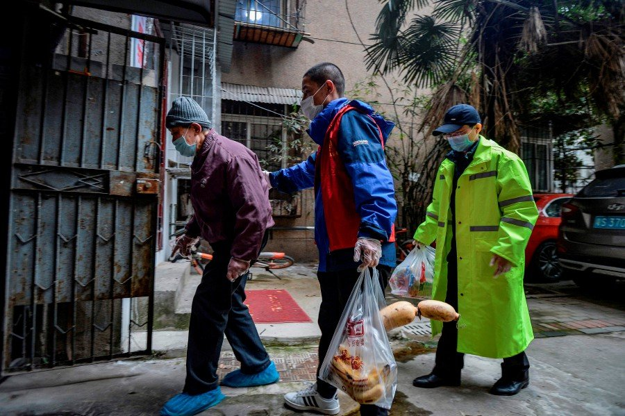This photo taken on March 16, 2020 shows community volunteers escorting an elderly resident back home after receiving an order of food and vegetables in Wuhan, China's central Hubei province. - AFP pic