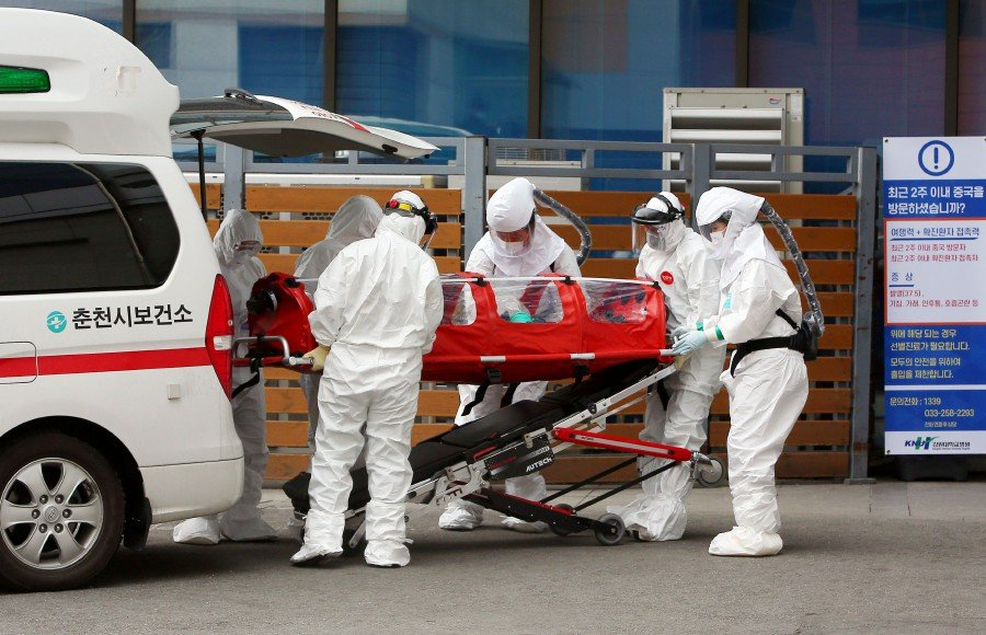 Medical workers wearing protective gear carry a patient infected with the Covid-19 coronavirus at a hospital in Chuncheon. -YONHAP/AFP
