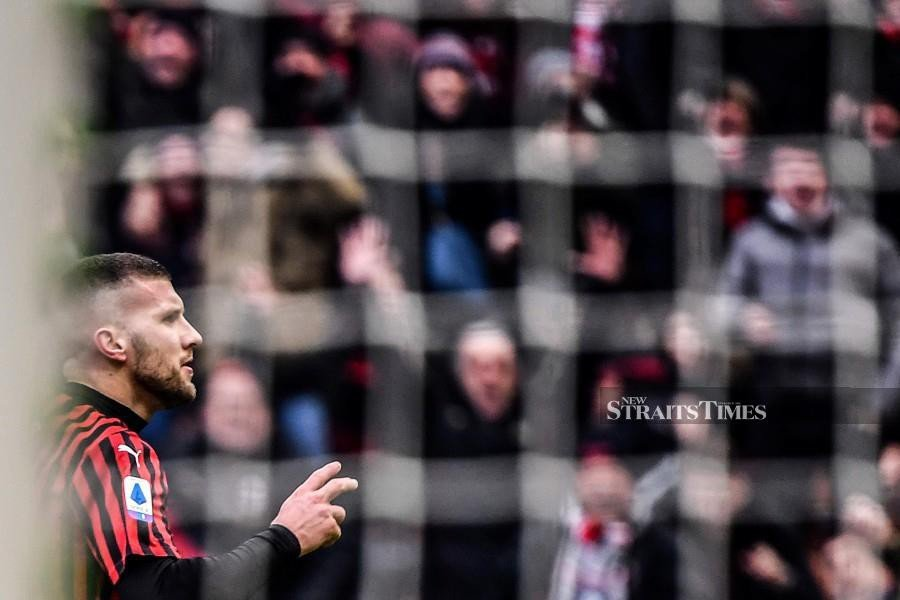 AC Milan's Croatian forward Ante Rebic (L) celebrates after scoring a last second winning goal during the Italian Serie A football match AC Milan vs Udinese on Jan 19, 2020 at the San Siro stadium in Milan. Photo: AFP