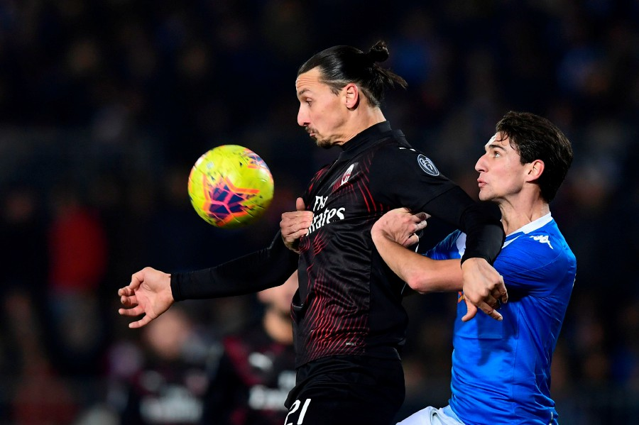 AC Milan's Zlatan Ibrahimovic (left) fights for the ball with Brescia's Andrea Cistana during the match at the Mario Rigamonti stadium in Brescia. - AFP