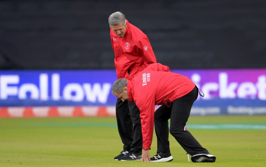 Umpires Richard Illingworth (right) and Richard Kettleborough inspect the outfield as rain stops play during the 2019 Cricket World Cup first semi-final between India and New Zealand at Old Trafford in Manchester. - AFP