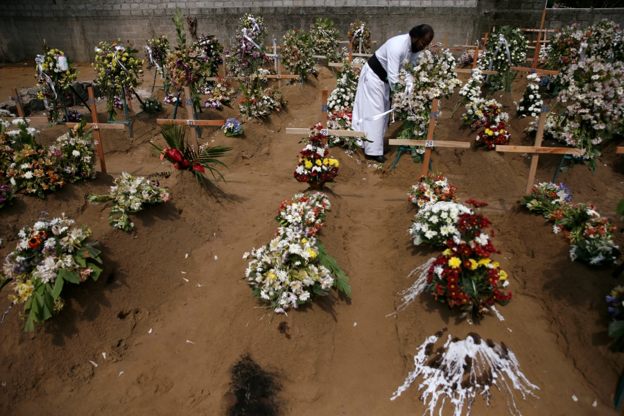 A priest arranges flowers at the site of a mass burial in Negombo, Sri Lanka.-Reuters