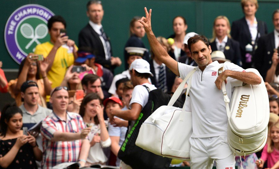 Switzerland's Roger Federer (right) waves as he leaves the court after beating France's Lucas Pouille (left) during their men's singles third round match on the sixth day of the 2019 Wimbledon Championships at The All England Lawn Tennis Club in Wimbledon, southwest London. - AFP