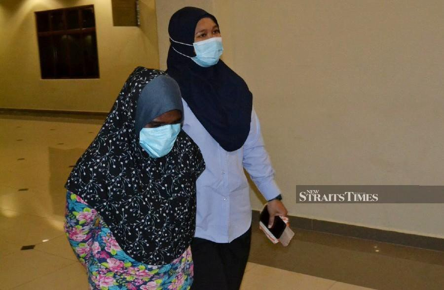 Khairunnisa Abdullah (left) was charged with abusing a 9-year-old girl under her care by pressing a hot knife to the child's arm until she suffered physical injuries. - Photo by ASROL AWANG/NSTP