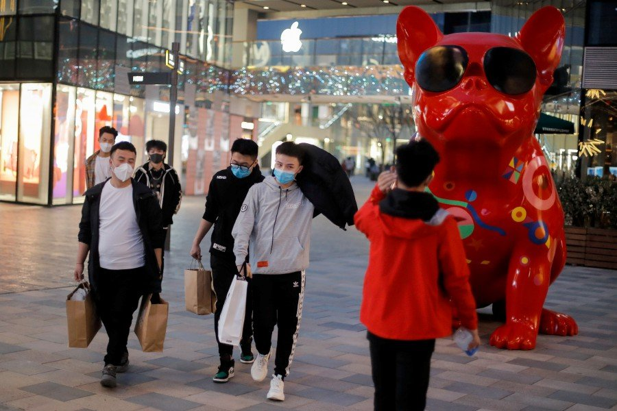 People wearing protective masks walk in a shopping district in Beijing, China. -REUTERS pic