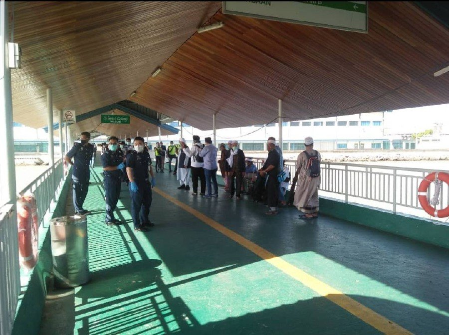 Some of the participants of a tabligh gathering in Seri Petaling being escorted by police at Tawau Ferry Terminal for screening. -- Pix courtesy of NST reader.