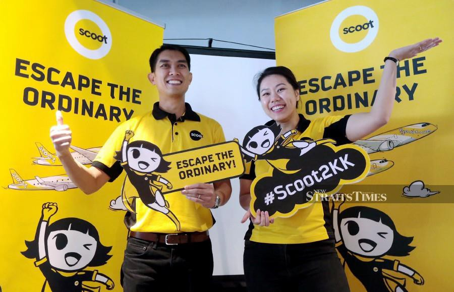 Scoot Chief Commercial Officer Calvin Chan (right) and staff Lau Liang Tong holding the low-cost arm of Singapore Airlines Group's promotional materials after the official launch of its first direct flight between Singapore and Kota Kinabalu in Kota Kinabalu. (NSTP/EDMUND SAMUNTING)