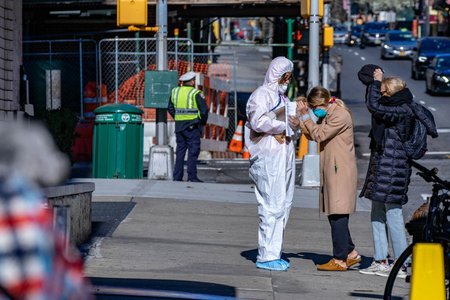 A Animal Medical Center employee wears a hazmat suit as she collects a pet from their owner and ushers them into the hospital as part of precautions against COVID-19 on March 24, 2020 in New York City. - AFP pic