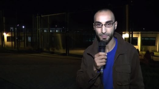"""In this image grab taken from a video on March 26, 2016 shows Faycal Cheffou, one of the main suspects of the Brussels attacks, speaking in a video posted on YouTube in 2014 in which he calls himself an independent journalist demanding the authorities respect the rights of asylum-seekers. Faycal Cheffou, believed to be the """"man in a hat"""" pictured in CCTV footage alongside the two airport bombers, but whose device did not go off, is the first person to face terrorist offences over the bloodiest attacks ever to strike the symbolic capital of Europe."""