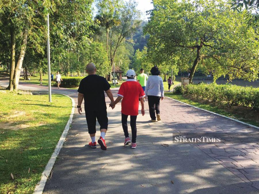 A picture of the writer's brother accompanying their mother during one of their walks at the park shortly after being diagnosed with cancer. PIC COURTESY OF WRITER