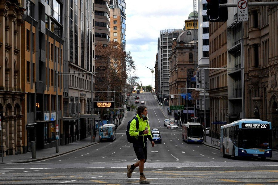 A man walking through the quiet streets of the central business district as a lockdown in Australia's largest city Sydney was tightened. - AFP Pic