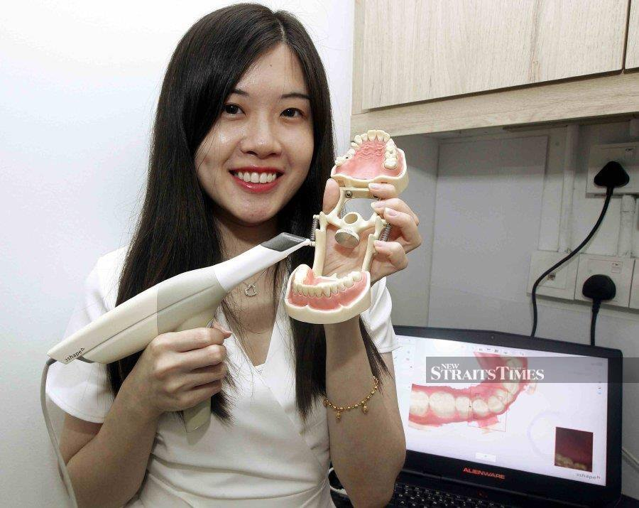 Dr Melissa Lee Rong showing the scanner used to make a 3D model of patients' teeth.