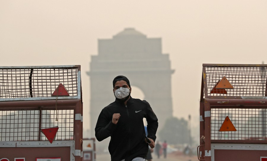 A man wearing a mask runs past the India Gate on a smoggy morning in New Delhi, India. -Reuters