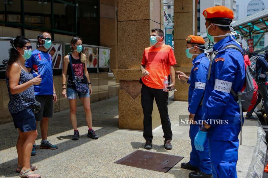 This March 20 file pic shows Civil Defence Force personnel speaking to tourists in Kuala Lumpur, amid the Movement Control Order. - NSTP/AIZUDDIN SAAD
