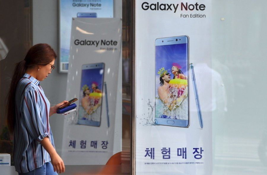 A woman walks past advertising showing the Samsung Galaxy Note Fan Edition smartphone at a Samsung mobile store in Seoul. AFP