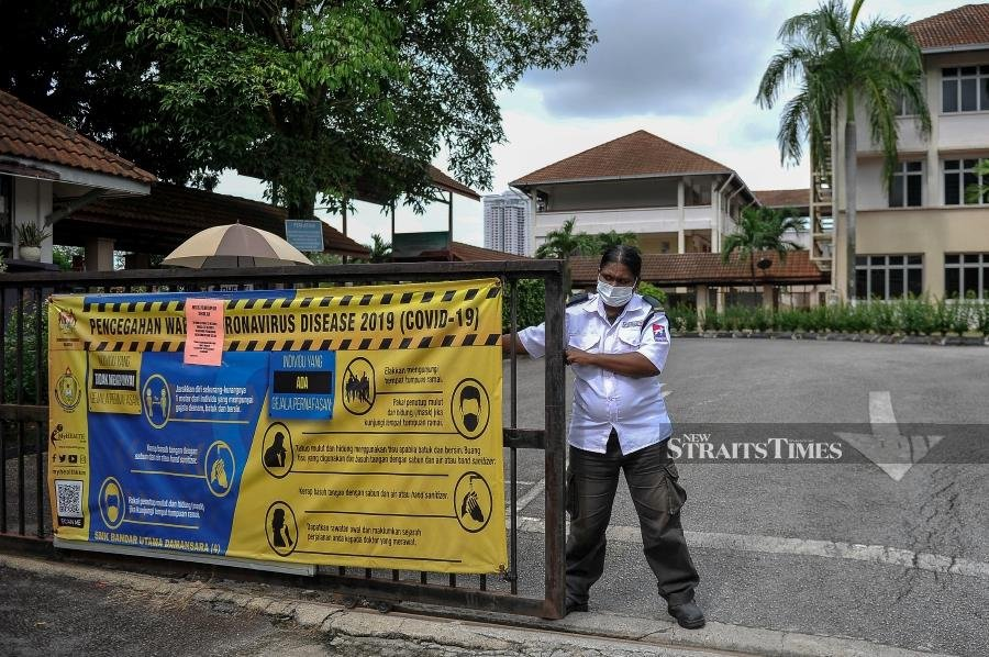 A security officer closes the gate of SMK Bandar Utama Damansara (4) after Petaling was placed under Red Zone on Oct 12. - BERNAMA pic