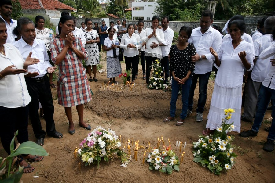 Family members pray for their mother, a victim of the suicide attacks on churches and luxury hotels, at the site of a mass burial in Negombo, Sri Lanka.-Reuters