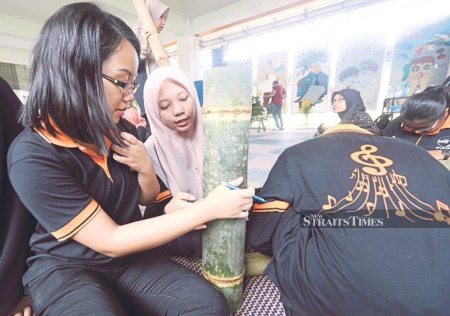 Universiti Malaysia Kelantan Faculty of Creative Technology and Heritage students making a traditional musical instrument using bamboo during a programme.