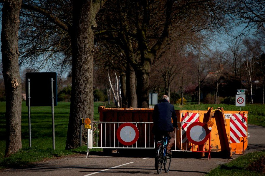 A cyclist rides at a police blockade made with containers on the alternative border crossings between Belgium and the Netherlands, in Hoogstraten. -AFP pic