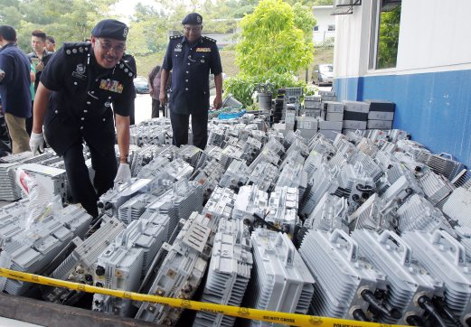 Shah Alam district police chief ACP Shafien Mamat (left) shows some of the telecommunication equipment seized from the two suspects. Pix by INTAN NUR ELLIANA ZAKARIA.