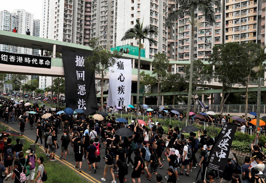 "Anti-extradition bill protesters march at Tseung Kwan O residential district in Hong Kong, China, August 4, 2019. The banners read ""Withdraw the evil law"" and ""Heartbroken"". — Reuters"