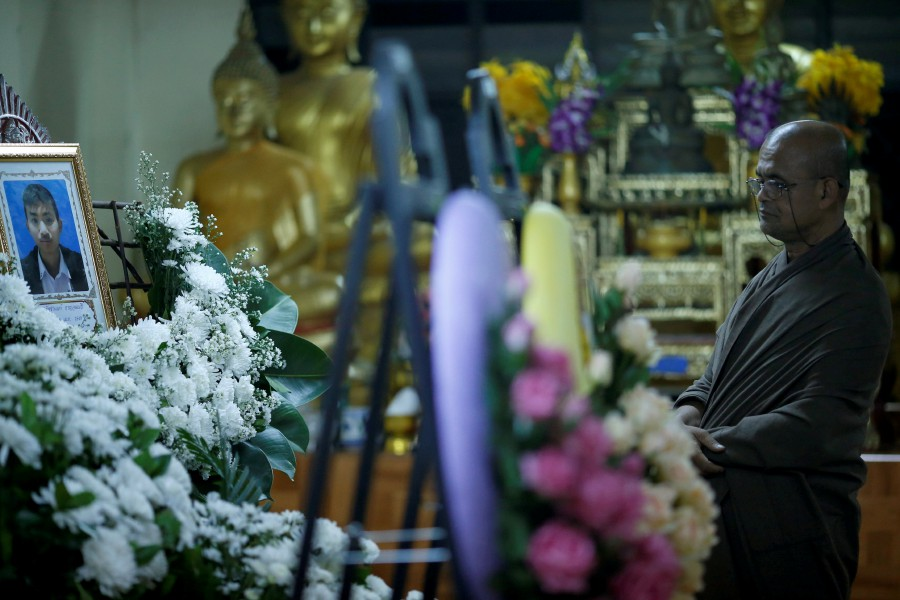 A buddhist monk stands near a portrait of Ratchanon Karnchanamethee, 13, who was killed in a mass shooting, during his funeral at a temple in Nakhon Ratchasima, Thailand. -Reuters